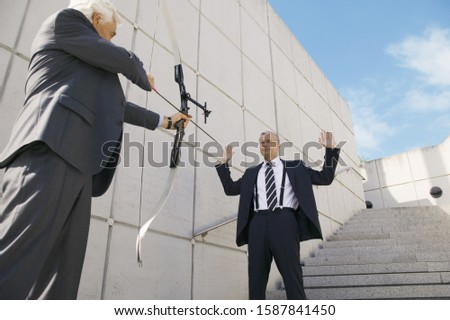 Businessman pointing bow and arrow at other businessman