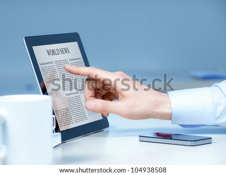 Businessman pointing on modern digital tablet with world news on screen at the workplace.