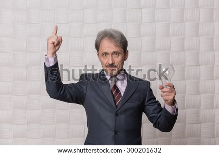 Businessman pointing out isolated on cream background. Mature man in grey business suit knows how to rule the company and be successful.