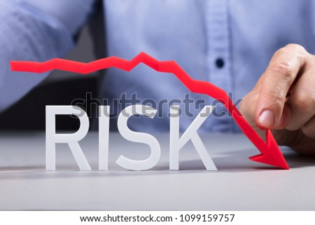 Businessman Pointing Red Diminishing Arrow Over The Risk Text On Reflective Desk