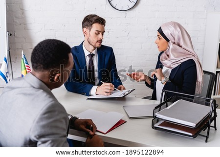 businessman pointing with pen at contract near arabian businesswoman and interpreter, blurred foreground Сток-фото ©