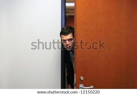 Businessman poking his head furtively through a doorway