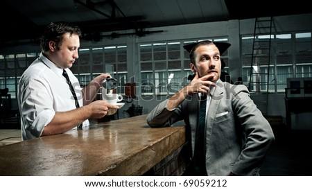 Businessman ponders as barista tops up his coffee mug - stock photo