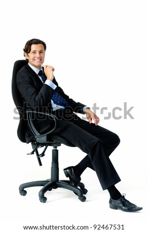 Businessman poses with pen while sitting on an office chair in studio, isolated on white