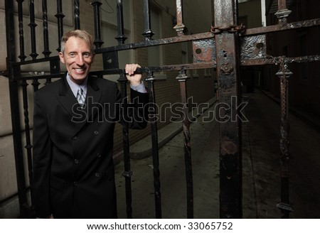 Businessman posing by an iron fence