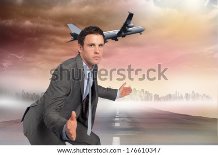 Businessman posing with hands out against road leading out to the horizon