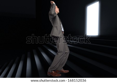 Businessman posing with hands up against steps leading to light in the darkness
