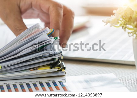 Businessman Preparing reports papers with graphs, charts on Stacks of documents files for finance in office. Piles unfinished achieves with paper clip near computer. Concept of Business Annual Report. #1214053897