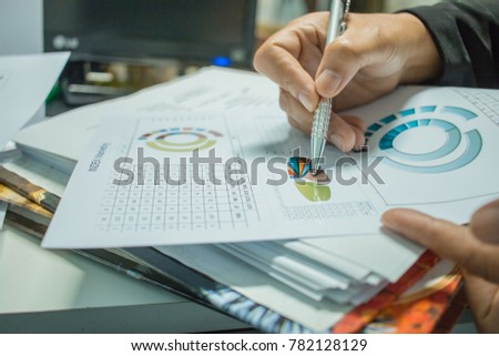 Businessman Preparing reports papers with graphs, charts on Stacks of documents files for finance in office. Piles of unfinished document achieves with paper clip. Concept of Business Annual Report. #782128129