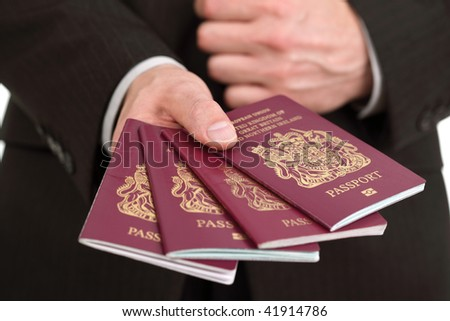 Businessman presenting four British passports at customs or check in area - stock photo