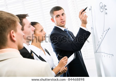 Businessman presenting his ideas on whiteboard to colleagues - stock photo