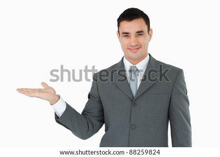 Businessman presenting something in his palm against a white background
