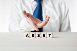 Businessman presenting the wooden cubes with the word asset. Business asset management concept.