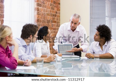 Businessman presenting to colleagues on laptop