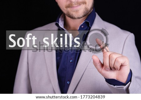 Businessman presses a button with the text SOFT SKILLS. Business concept.