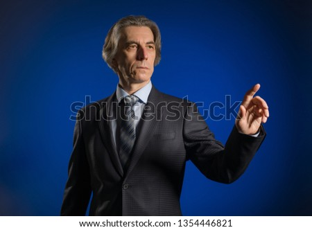 Businessman presses a virtual button on a dark background. #1354446821