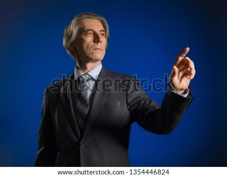 Businessman presses a virtual button on a dark background.