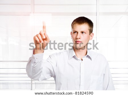 businessman pressing a touchscreen button on a office background