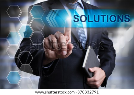 "Businessman pressing button on touch screen interface and select ""Solutions"". Business concept. Internet concept."