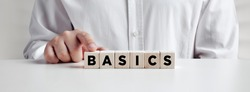 Businessman pressing his finger on the wooden cubes with the word basics. Back to basics, simplification in business or education concept.