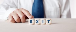 Businessman pressing his finger on the wooden cubes with the word exit. Business exit strategy.