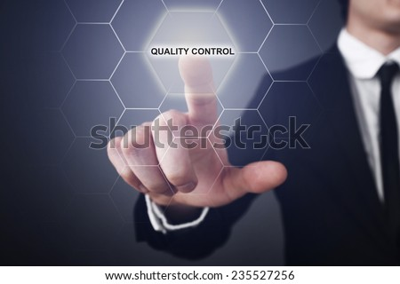 Businessman pressing touch screen interface and and selects the quality control