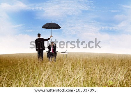 Businessman protect his partner by using an umbrella,