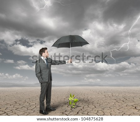 Businessman protect with umbrella a plant to help the agriculture