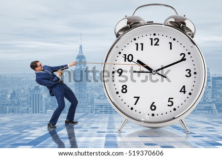Businessman pulling clock in time management concept #519370606