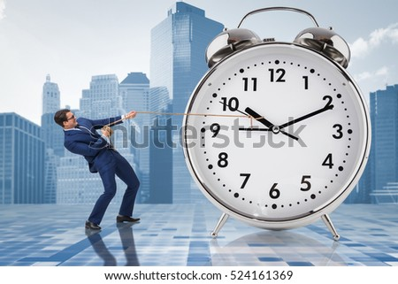 Businessman pulling clock in time management concept #524161369
