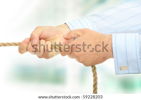 Businessman pulling on a piece of rope.
