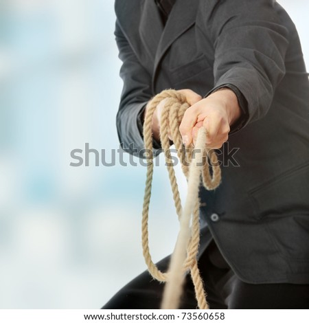 Businessman pulling on a rope.