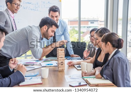Businessman pulling out or placing wood block on the tower in modern office. plan and strategy in business.