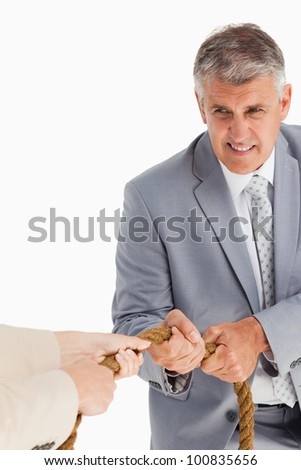 Businessman pulling the rope against white background