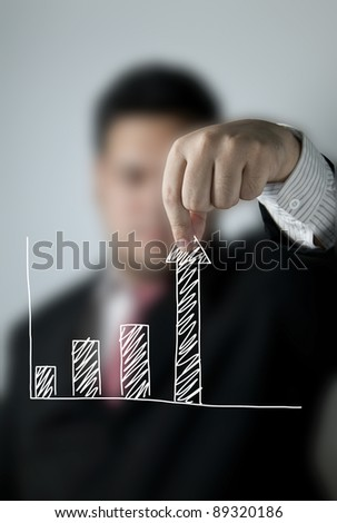 Businessman pulling up a bar from a graph