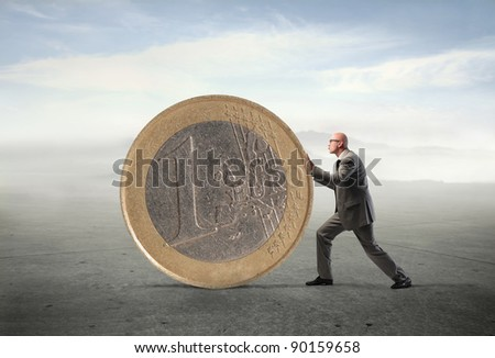 Businessman pushing a giant euro coin