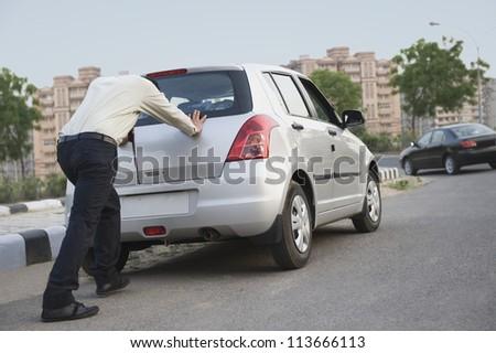 Businessman pushing his car - stock photo
