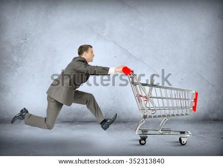 Businessman pushing shopping cart on grey wall background