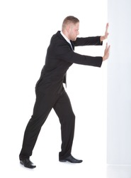 Businessman pushing the edge of a blank white sign leaning his weight against it  full length on white with just the edge of the sign visible