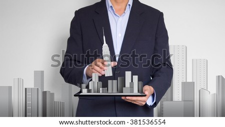 Businessman put in a building model on tablet computer. Town model on tablet computer. investment concept.