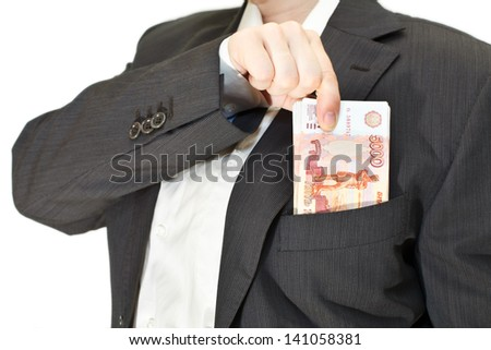 Businessman puts a pile of money in the pocket of his suit