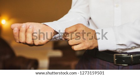 Businessman puts on a white formal stylish shirt. Formal style. Businessman in a classic formal jacket