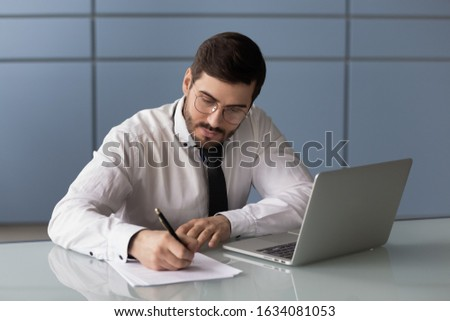 Businessman puts personal signature signs documents do paperwork, writing business letter seated at workplace desk. Focused office worker noting thoughts ideas busy fruitful workday brain work concept Сток-фото ©