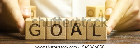 Businessman puts wooden blocks with the word Goal. The concept of achieving business goals. Reaching new heights. Execution of a business plan. Purposefulness. Perseverance. Target. Planning