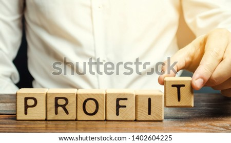 Businessman puts wooden blocks with the word Profit. The financial result of the company for a certain period of time. Income. Return on investment. Performance. Profitable business. ROR, ROI #1402604225