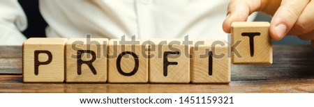 Businessman puts wooden blocks with the word Profit. The financial result of the company for a certain period of time. Income. Return on investment. Performance. Profitable business. ROR, ROI #1451159321