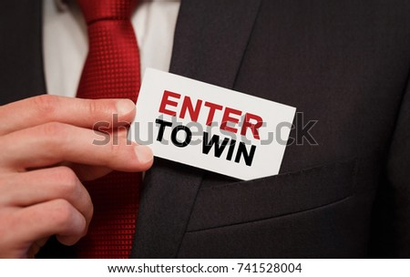 Businessman putting a card with text Enter to Win in the pocket #741528004
