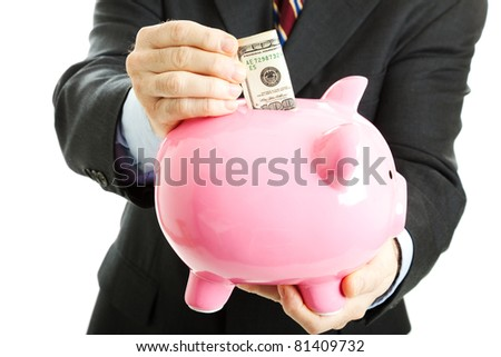 Businessman putting a hundred dollar bill in his piggy bank.  White background.