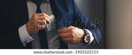 Businessman putting banknotes of dollars  in suit pocket. Corruption concept with  copy space Сток-фото ©