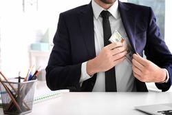 Businessman putting bribe in pocket indoors